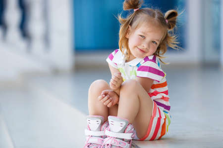 Cute little red-haired girl with hair in two ponytails, grey eyes and sweet smile, dressed in a multicolored striped dress with short sleeves, learning to roller skate in the city in the fresh air in the summer Stock Photo