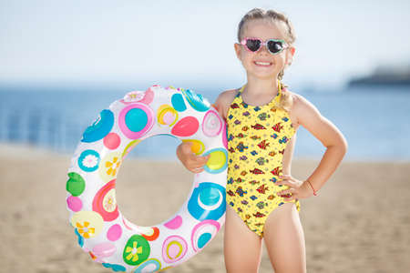 sandcastles: Little girl with pigtails, wearing sunglasses in the shape of hearts, dressed in a yellow swimsuit with colorful fishes, in the hands holding a large, inflatable, colorful lifebuoy, is on a sandy beach on the calm blue ocean Stock Photo