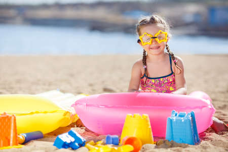 sandcastles: Cute little girl with pigtails, wearing sunglasses in the shape of hearts, dressed in a yellow swimsuit with colorful fishes, plays in the sand on a tropical beach with plastic colorful toys in the background of the calm blue ocean