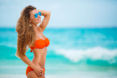 Happy young woman with long blonde hair, a beautiful smile and white straight teeth, standing on white sand tropical beach near the blue ocean, wearing a bikini is orange, wears blue mirrored sunglasses, ears wearing gold earrings