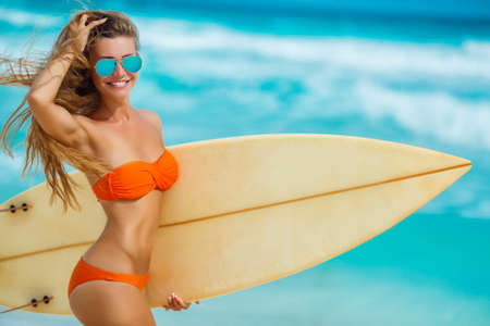 Girl of the European appearance with a beautiful figure in mirror sunglasses blue, brunette with long hair in bikini orange, posing against the backdrop of the blue ocean with the white foam of the waves, keeps on hand a surfboard