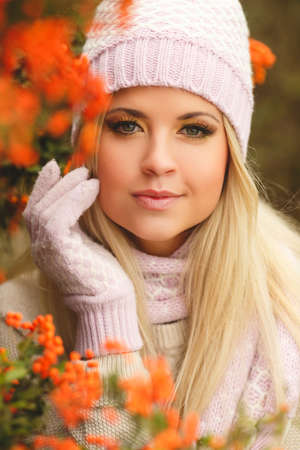 Beautiful young woman with long blonde straight hair, light makeup, wearing a light sweater, pink scarf and gloves, on his head wearing a pink and white knitted cap, spends time outdoors in the Park in the middle of autumn near bushes of ripe red Rowan Stock Photo