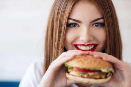 Beautiful woman with red long straight hair, bright make-up, brown eyes, red lipstick, long eyelashes, pink nail polish in the hands holding a large hamburger, sitting at a table in a cafe, dinner alone Stock Photo