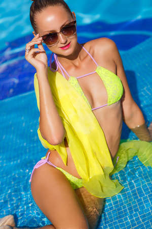 A young woman with a beautiful figure, brunette with elegant hair, ear wearing earrings, is wearing dark sun glasses and a bikini is yellow, on the shoulders draped a yellow pareo, spends time in the pool with blue water in the summer