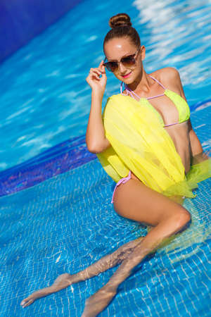 bronzed: A young woman with a beautiful figure, brunette with elegant hair, ear wearing earrings, is wearing dark sun glasses and a bikini is yellow, on the shoulders draped a yellow pareo, spends time in the pool with blue water in the summer