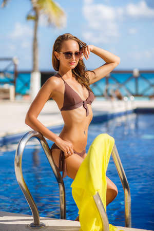 pareo: Beautiful young woman with a slender figure, brunette with long flowing hair, wearing earrings ears, wearing dark sun glasses and bikini in brown, standing on the steps of the pool with silver rails on which hangs a yellow pareo Stock Photo