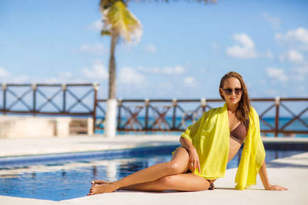 pareo: A slender young woman with a nice figure, brunette with long flowing hair, wearing earrings ears, wearing dark sun glasses and bikini in brown on the shoulders draped a yellow pareo, spends time near the pool with blue water in the summer