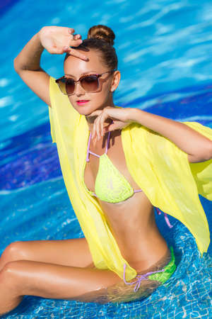 pareo: A young woman with a beautiful figure, brunette with elegant hair, ear wearing earrings, is wearing dark sun glasses and a bikini is yellow, on the shoulders draped a yellow pareo, spends time in the pool with blue water in the summer