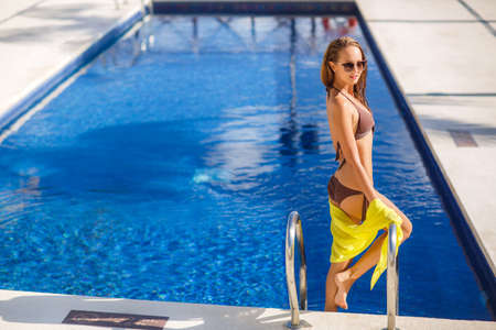 pareo: A slender young woman with a nice figure, brunette with long flowing hair, wearing earrings ears, wearing dark sun glasses and bikini in brown, hand holds yellow pareo, spends time near the pool with blue water in the summer