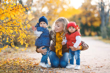 Young beautiful woman with long curly blond hair and blue eyes, wearing blue jeans and brown boots on his neck and orange scarf, walking in yellow autumn park with two young girls, dressed in blue jeans, a red and a blue jacket and cap Stock Photo