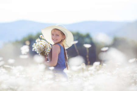daisie: Girl, brunette with long hair braided in two braids, a large white straw hat, blue overalls, in the ears is a small earring, spending time alone in the highlands on a flowering field white daisy outdoors during the summer, in the hands holding a bouquet