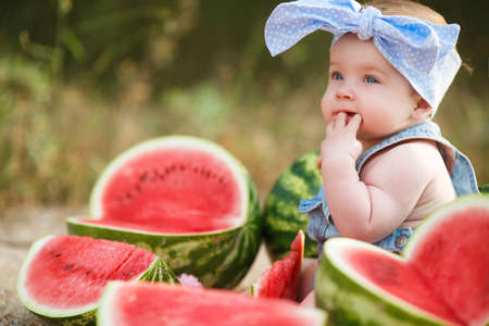 bandana girl: Little cheerful girl with gray eyes, in blue denim overalls and a blue bandana on his head tied with a bow, sitting on the ground in the garden next to the large cut, ripe red, juicy watermelons Stock Photo