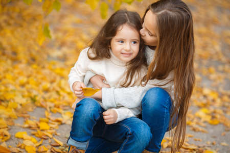 Two sisters, girls Oriental appearance, long blond hair, both dressed in light sweaters, blue jeans and brown shoes, spend time in the beautiful yellow autumn Park together, playing and having fun in the alley strewn with yellow leaves