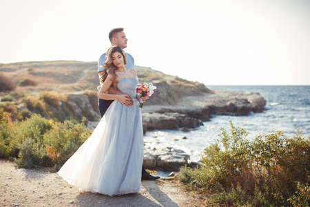 arm bouquet: A young couple in love, bride and groom, in their wedding clothes, standing arm in arm on top of the cliffs against the blue of the ocean outside in the summer time, in the hands of the bride has a beautiful wedding flower bouquet with white Lily