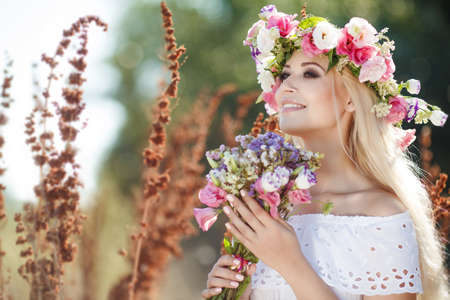 Young woman with long blonde straight hair, beautiful makeup and a nice smile, straight white teeth, dressed in a light white sundress, on his head wearing a wreath of colorful flowers, posing outdoors in a lush field with a bouquet of wildflowers Stock Photo