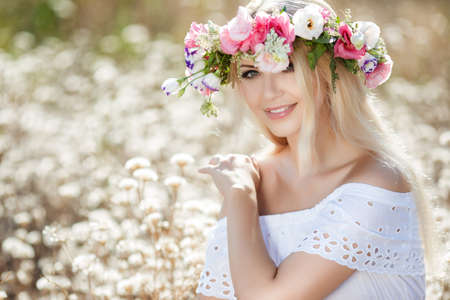 Summer portrait of a beautiful blonde woman with long straight hair, beautiful makeup and a nice smile, straight white teeth, dressed in a light white sundress, on his head wearing a wreath of colorful flowers posing outdoors in flowery field