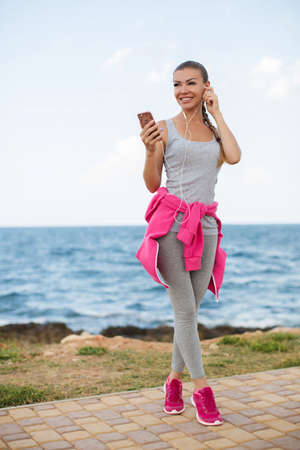 Young beautiful woman with athletic build, brunette with hair gathered at the back, light makeup, wearing a gray shirt and gray sweat pants, tied at the waist sports jacket pink, listening to music with headphones standing on beach