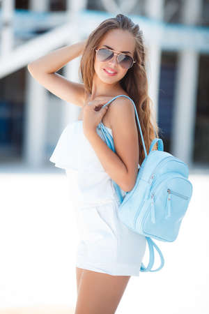 birthmark: Young beautiful brunette woman with brown long hair, sun glasses, pink lipstick, attractive birthmark near his lower lip, a blue backpack, dressed in a short white suit, posing outdoors in the summer on a white platform near the white wooden steps