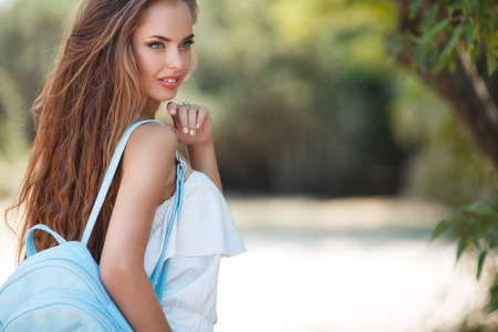 Young beautiful brunette woman with long wavy hair and gray eyes, light makeup, pink lipstick dressed in a white blouse, on her shoulder is a small blue backpack, posing on a walk outdoors in green summer Park