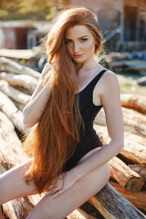 thick hair: Portrait of sexy redheaded woman, long thick hair, the freckles on the face and body, big lashes and beautiful eyebrows, dressed in black closed swimsuit, slender beautiful figure posing outdoors in the summer in the countryside on a country ranch Stock Photo