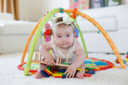 A little girl of 8 months, blonde hair tied with a white ribbon with a flower white rose, blue eyes, wearing a white T-shirt and panties, playing in the bright childrens room on the floor with their many-colored toys on a white soft carpet Stock Photo