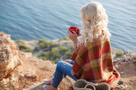 Portrait of beautiful woman with long blonde curly hair, sitting on a rock on a rocky shore in the background of the calm blue sea, on the shoulders draped a blanket, holding a Cup of hot tea, dressed in blue jeans, standing next to the basket