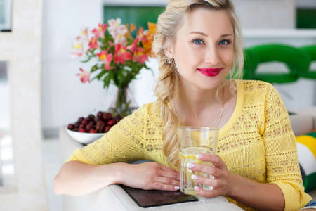 Young beautiful blonde woman with blue eyes, light make-up, bright red lipstick, beautiful manicure, wearing gold jewelry, sitting on a bright kitchen with a glass of water with lemon, dressed in a yellow blouse, portrait of a housewife Stock Photo