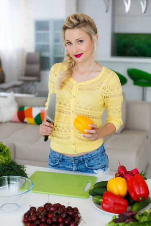 Young, beautiful, slender woman, housewife, blonde with blue eyes, light makeup, bright red lipstick, wearing jewelry, wearing a yellow blouse and blue jeans, is in the large bright kitchen is slicing vegetables for the preparation of dietary salad Stock Photo