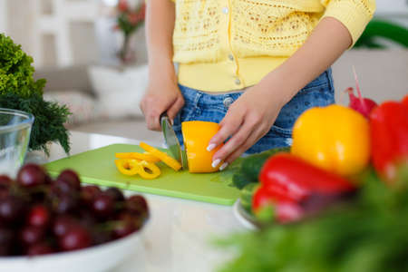 cuchillo de cocina: The hands of a young slim woman dressed in a yellow blouse and blue jeans, working on a large bright kitchen cutting fresh vegetables for preparation of dietary salad a large kitchen knife on the table are cherry, parsley, radishes, yellow and red pepper Foto de archivo