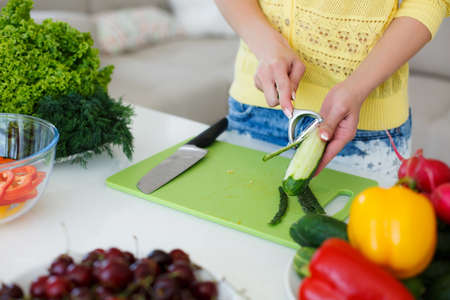 Hands of a young slim woman wearing a yellow shirt and blue jeans, dealing with a large bright kitchen cutting fresh vegetables for the preparation of dietary salad, cucumber cleans, are on the table cherries, parsley, radishes, yellow and red peppers