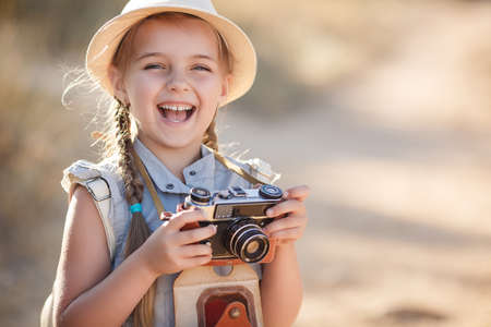 small world: Girl 6 years old with an old brown suitcase and an old camera in hand, brunette with two braids, wearing a straw hat against the sun in a blue flight suit, nature photographs while traveling, standing on a country road Stock Photo