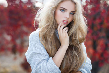 Autumn portrait of beautiful young woman with long blonde hair and blue eyes, dressed in gray-blue knitted sweater, light makeup, spends time alone outdoors in the Park, posing for photographer autumn among the trees and bushes with yellow and red leaves