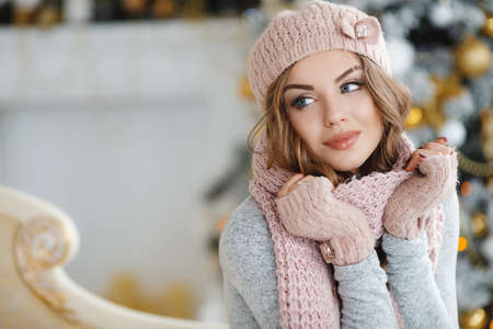 Red-haired beautiful young woman with blue eyes and curly long hair, in a beige knitted hat, scarf and gloves, beautiful makeup and large black eyelashes, purple nail Polish, posing in Studio on light background ornate Christmas tree with yellow balls Standard-Bild