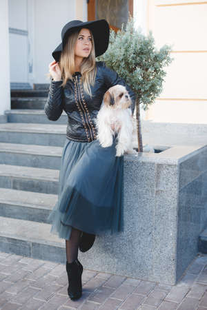 Beautiful woman with long blonde straight hair and grey eyes wearing a black hat with a large brim, a black leather jacket and long blue skirt, posing in the city with his friend, the dog breed Shih Tzu, the lady with the dog, walking outdoors in autumn Stock Photo