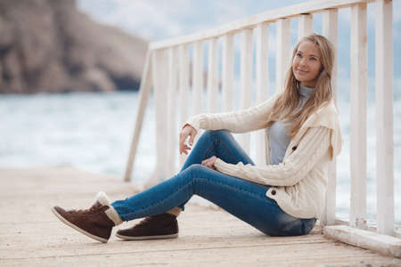 knitted jacket: Young woman with long straight blond hair and gray eyes, dressed in a white knitted jacket, a gray turtleneck and blue jeans, spending time alone, sitting on a white wooden wharf near the blue sea on a background of mountains