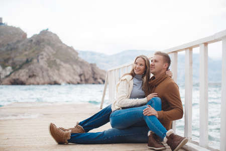 Young couple blond guy with short hair in a brown sweater and blue jeans and a blonde girl with straight long hair, dressed in a white jacket and gray turtleneck, spend time together, sitting, embraced on a white wooden pier near the sea in autumn