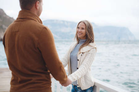 Young couple blond guy with short hair in a brown sweater and blue jeans and a blonde girl with straight long hair, dressed in a white jacket and gray turtleneck, spend time together, standing on a wooden pier near the sea in the autumn holding hands