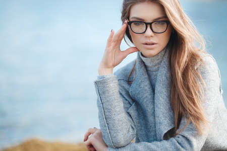 Stylish young woman model looks with long blond hair, wears black-rimmed glasses, slim figure, light makeup, dressed in a grey turtleneck and a grey coat posing on the street alone on a deserted beach on a blue sea background