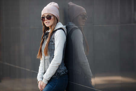 Young beautiful woman with model looks, beautiful makeup, pale pink lipstick, long red hair, wears dark sun glasses, wearing a light knitted sweater and denim vest, blue jeans and a pink sports hat posing on grey background in the city in the fall