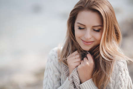 Spring portrait beautiful woman with blond, long, straight hair, big black eyelashes, drooping eyelids, light makeup, pink lipstick, wearing jewelry, wearing a knitted sweater is white with a large beige collar, posing outdoors in early spring. Imagens