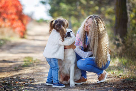 Family portrait of young blonde woman with long wavy hair and her little daughter, mother and daughter dressed in the same blue-white-pink sweater and light blue jeans, walking together with the dog breed Golden Retriever in a beautiful autumn Park