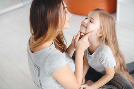 Happy mother and daughter, a woman with brown long hair, wearing jewelry, stretching her legs sitting on a white floor, on his mother's lap sits a daughter, a girl with long blond hair in a gray T-shirt and jeans, mother and daughter looking at each other