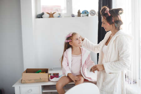 Mother and young daughter to make yourself a beautiful hairstyle, white bedroom near the window, helping each other, wind hair onto large pink curlers, both dressed in bright dressing gowns and bright t-shirts, girl sitting on a white table