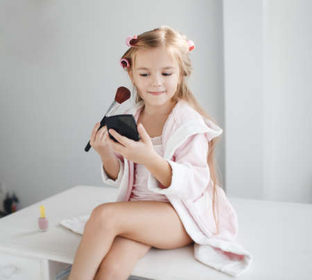 Little girl with long blond hair and brown eyes, wind the hair on the big pink curlers, holding in his hand a black powder compact and a large brush for makeup, sitting on a white table in front of the window, wearing a pink T- shirt and dressing gown