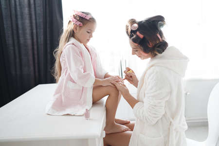 A young mother doing her nails to his little daughter pink nail Polish, a girl sitting on a white table in front of the window, putting their feet on mothers lap, mother and daughter are dressed in pink dressing gowns, the hair is wound on curlers