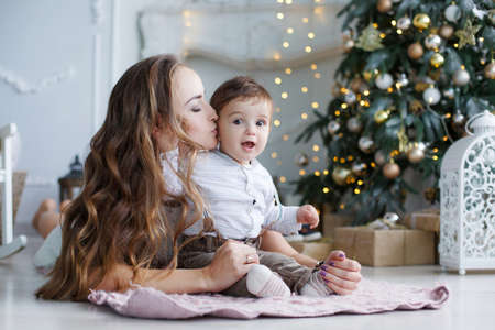 Beautiful brunette woman with long hair, dressed in a short white lace dress, holding New Years holiday lie on the floor next to a white elegant Christmas tree with his young son, the boy in pants and a shirt, Christmas portrait of mother and baby