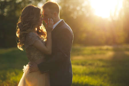 Beautiful young couple in love, bride and groom, the groom-brunette with short hair, dressed in a gray wedding suit and a white shirt, the bride a beautiful blonde with long curly hair, are embracing the rays of the setting summer sun in a Green park