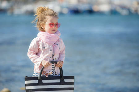 Beautiful little girl with blond hair, wearing pink glasses in the shape of hearts, big beach black and white striped bag, striped skirt, pink jacket, pink scarf, spending time alone outdoors on the beach in the afternoon, posing on blue ocean background