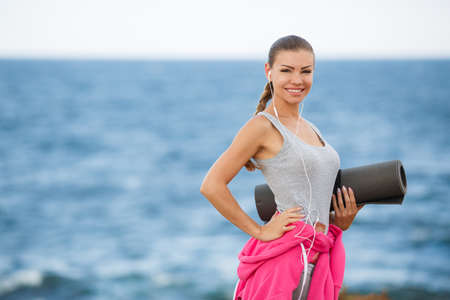tied in: A young woman, athletic, brunette with long hair braided in a braid, in a gray shirt and gray sweat pants, a belt tied a pink sports jacket, ready to perform fitness exercises on the beach in the fresh air on a dark gray mat that holds the left-hand Stock Photo
