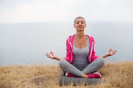 Athletic woman with a sweet smile, brunette, hair in a braid, full lips, wearing a gray t-shirt and gray sweat pants, pink sneakers and a pink sports jacket, performing relaxation exercises, sitting on a rocky beach Lotus position Stock Photo